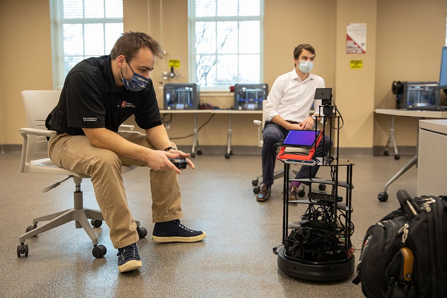 Glen Merritt and Braeden Given work with a robot UA researchers are developing.