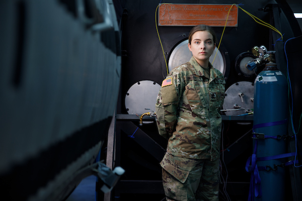A student in military uniform stands among industrial equipment