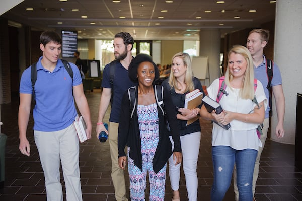 A group of law students walk through the law school lobby.