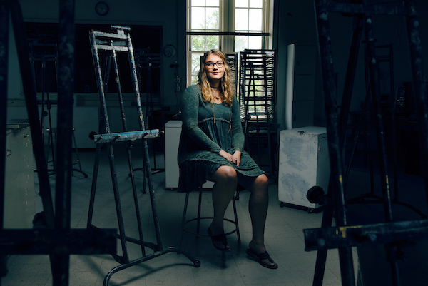 A student sits among easels and art supplies