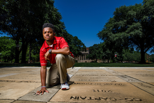 A student places their hand in the concrete handprints that surround denny chimes.