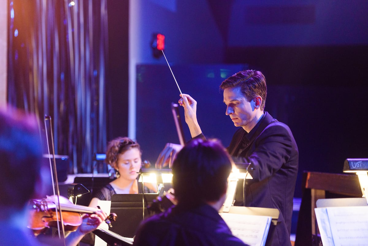 A conductor leads a student orchestra