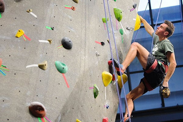 A student scales the rock climbing wall at the Student Recreation Center