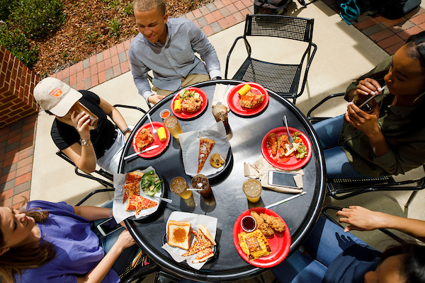 Students eat and chat outside at Fresh Food Company
