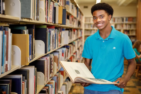 An early college student browses a library collection