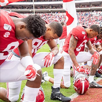 Football players kneel in prayer at the goal line at Bryant-Denny stadium