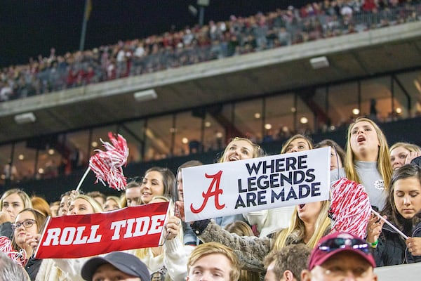 Fans in Bryant-Denny stadium hold up Where Legends Are Made banners