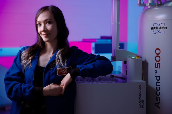 A student leans against lab equipment