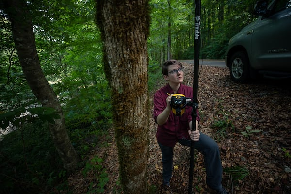 A researcher uses GPS in Alabama forest land.