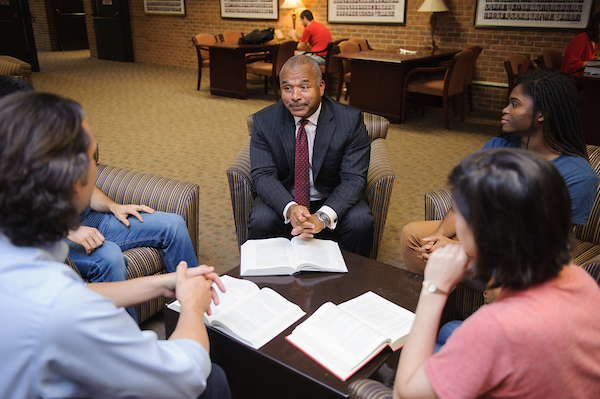 Law students discuss course material with a faculty member