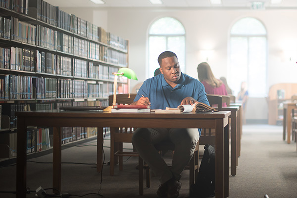 A student studies at a table in the Bruno Business Library