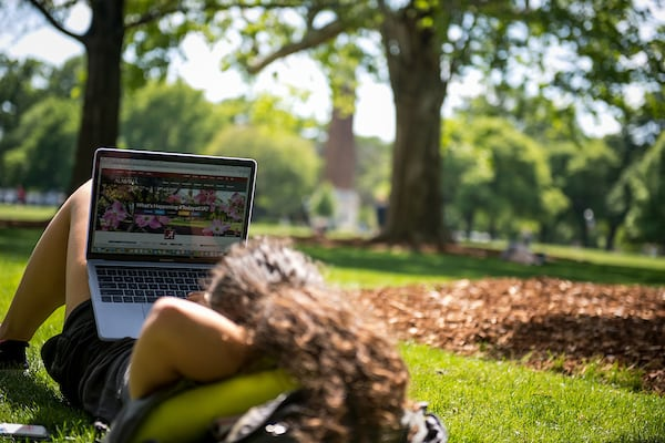 A student relaxes on the quad with her laptop.