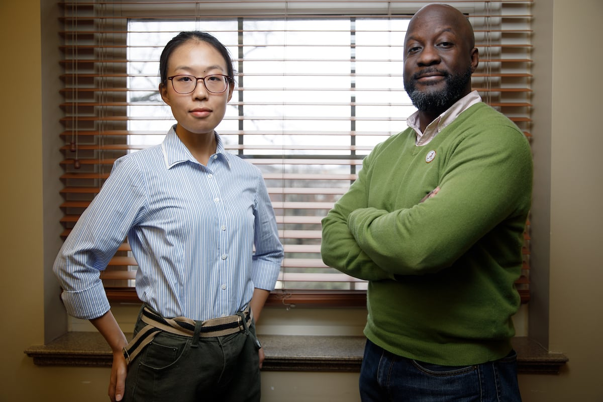 Two professors stand in front of a window.