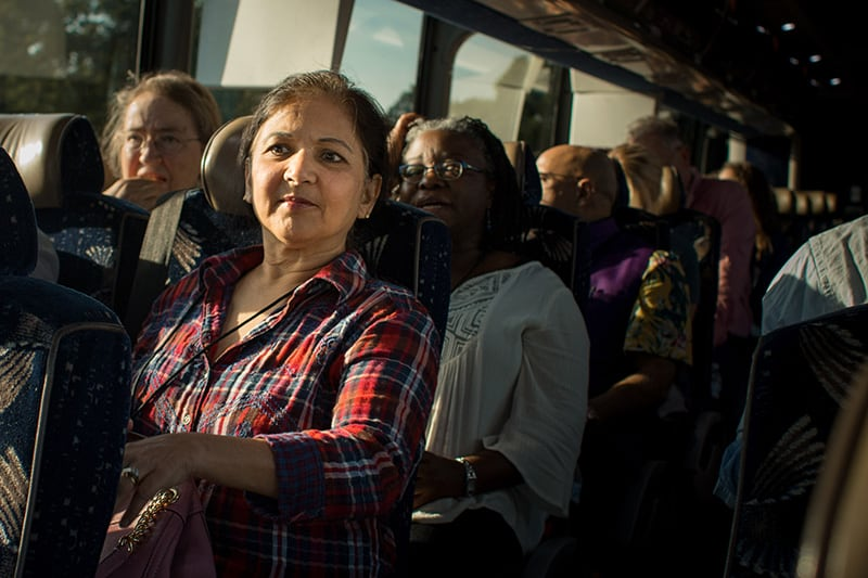 A group of new faculty members sit together on a bus