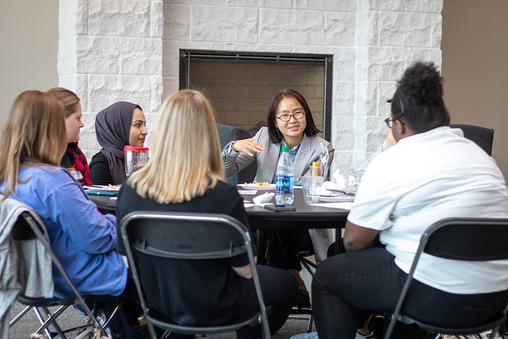 Students sit around a table during a cultural discussion event