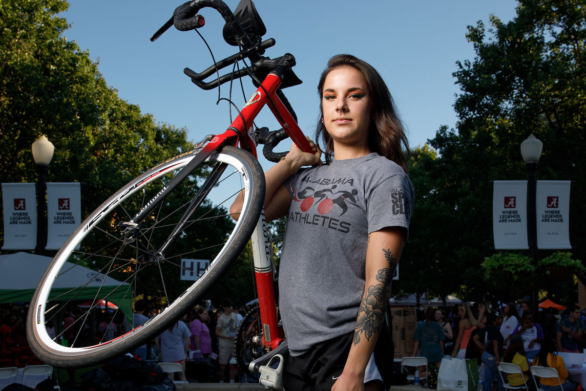 A student representing the spin club holds her bicycle