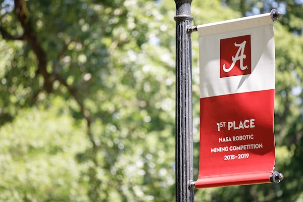 A banner celebrating UA's 1st place finish in NASA's robotics competition hangs on a light post