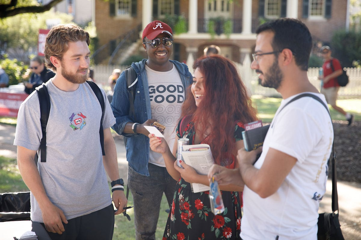 students converse in front of gorgas library