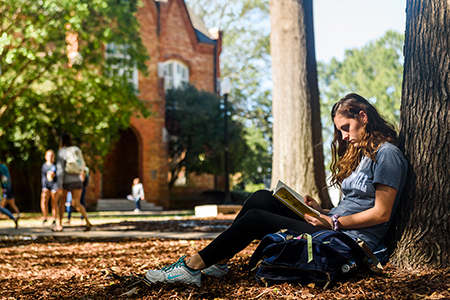 a student works on her laptop beneath denny chimes