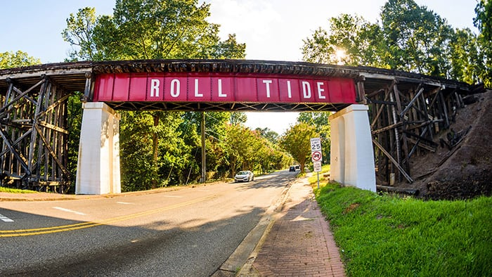 A bridge painted red with the words Roll Tide