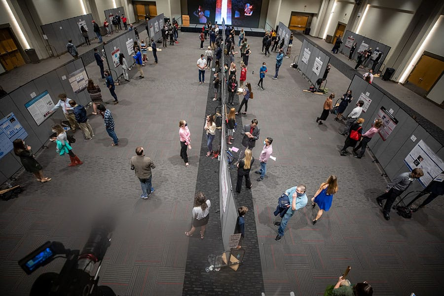 Students interact with visitors in an exhibition hall