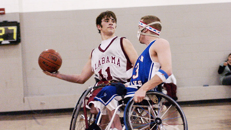 Two wheelchair basketball players playing basketball