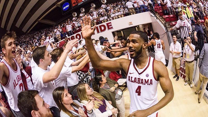 Fans high five a basketball player