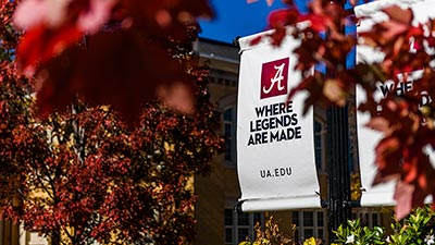 Outside banner for Legends campaign in the fall with red leaves in the forground.