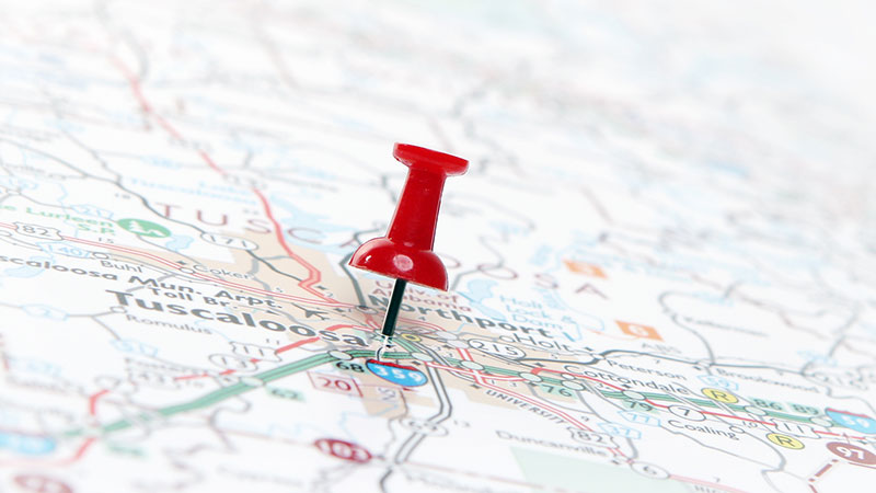 A flat map of the city of Tuscaloosa with a red push pin in the center of it.