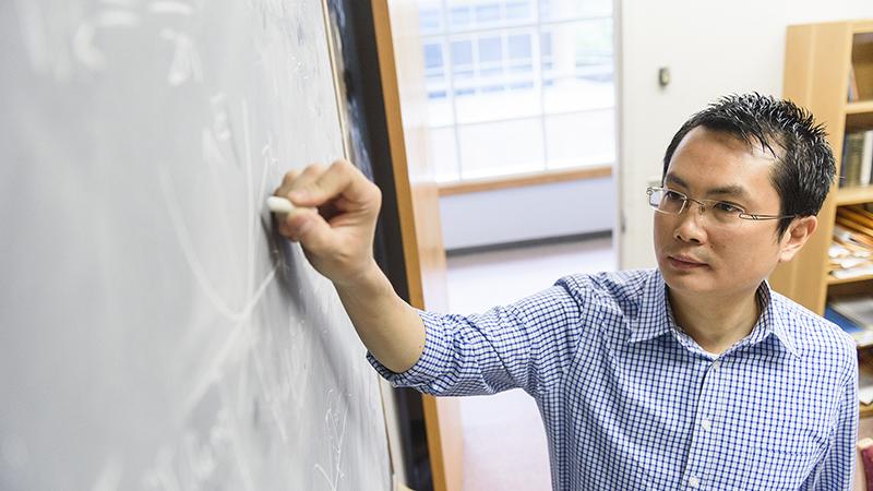 Professor writing on chalkboard