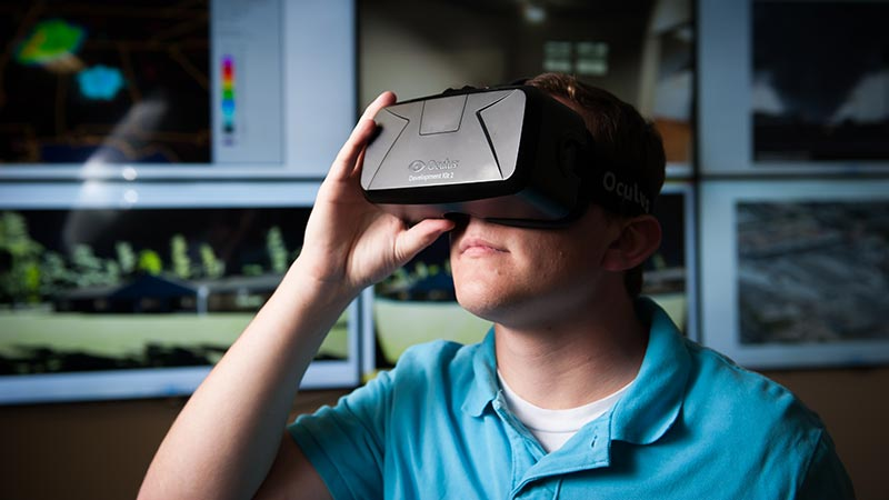 In a campus lab, Dr. Rick Houser, an education researcher, and Dr. Brandon Dixon, a computer scientist, use virtual reality technology to simulate high-thrill activities.