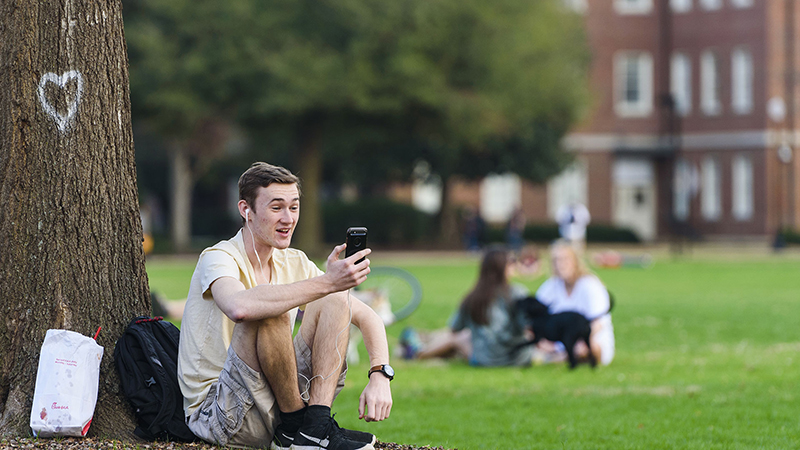 Students using a smartphone on the Quad