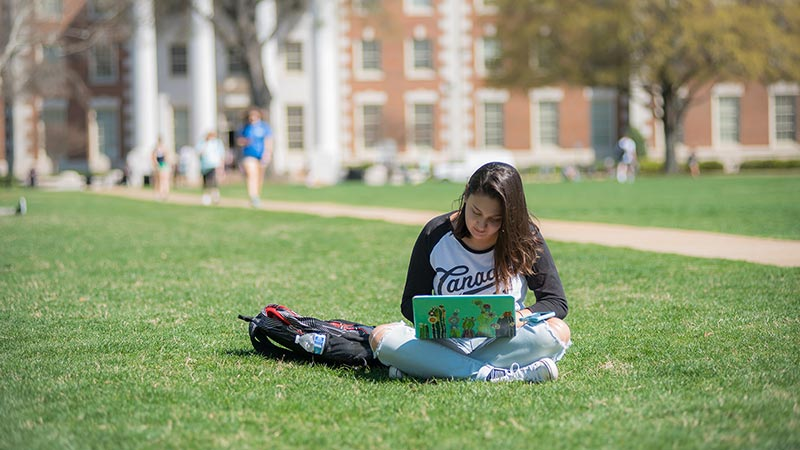 Students participating in an online class while relaxing on the Quad