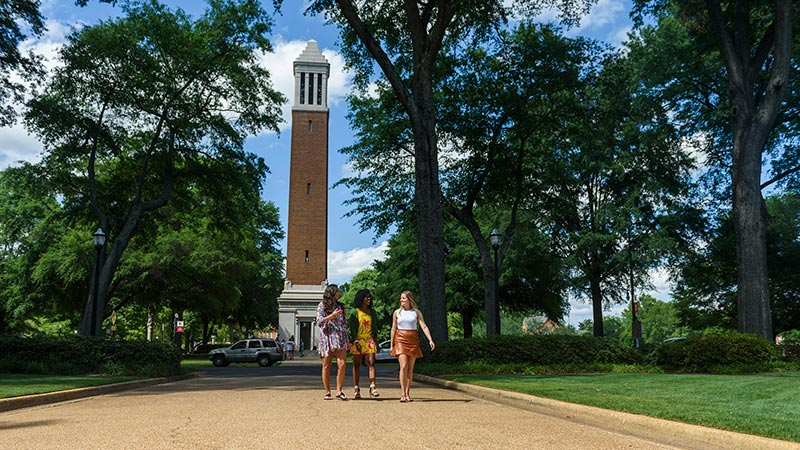 Students walking in the shadow of UA's historic Denny Chimes