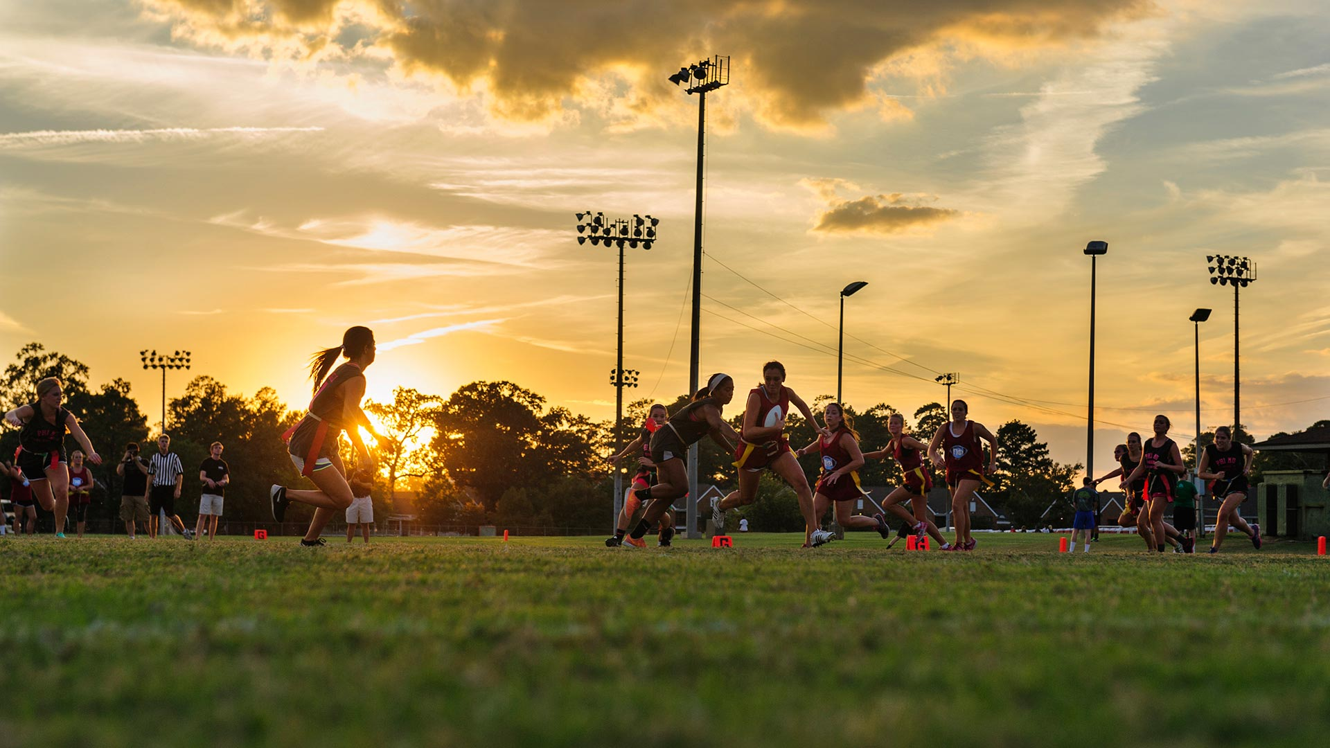 Students playing flag football at sunset
