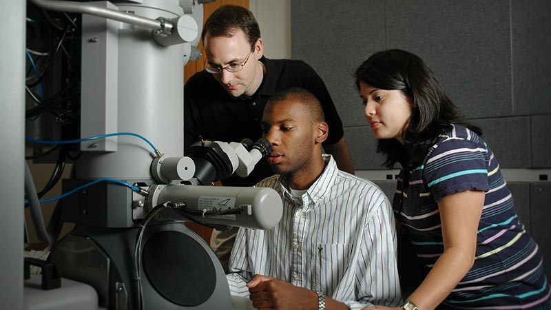 An instructor and students viewing the results of an experiment