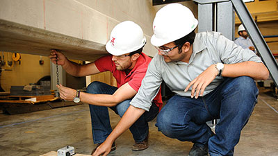 Two students in construction helmets stooping to look at a chain under a cement structure.