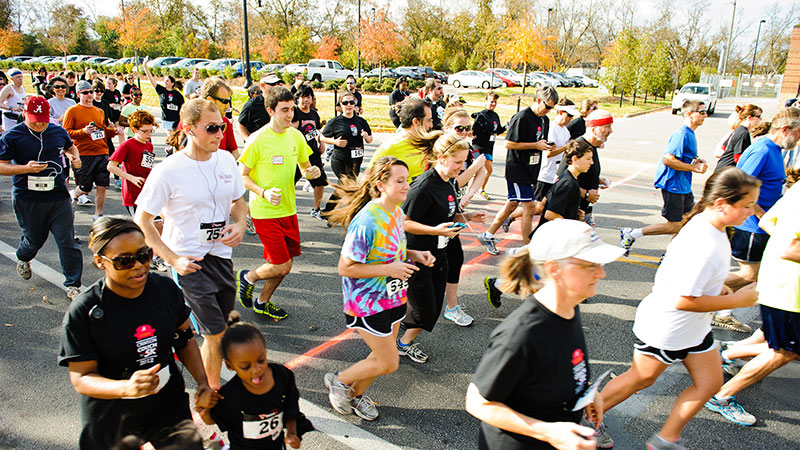 Students running in a road race on campus