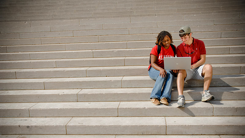 Students sitting on the library steps using a laptop