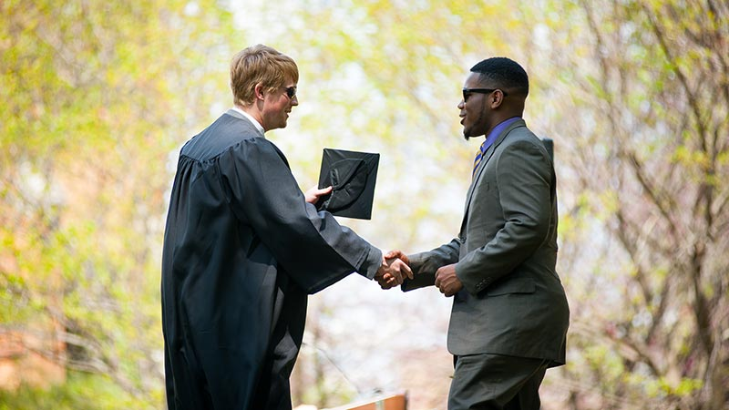 A graduate shakes hands with a classmate
