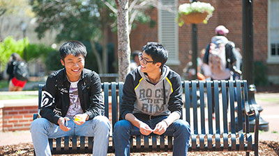 Two students talking outside on a bench.
