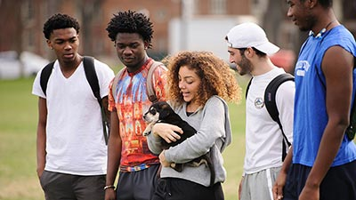 Students walking and holding a dog on campus