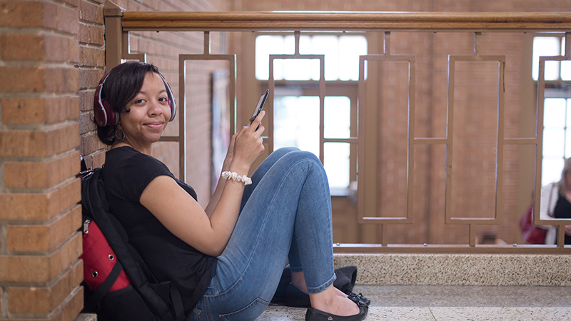 Student sitting with phone