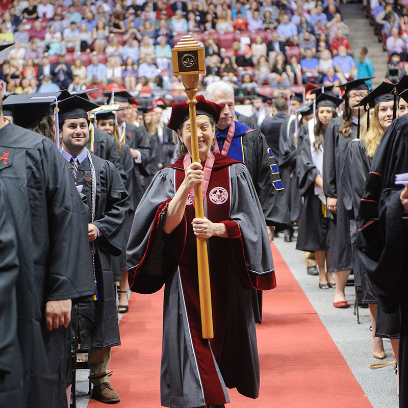 A professor carries The Ceremonial Mace into a commencement ceremony