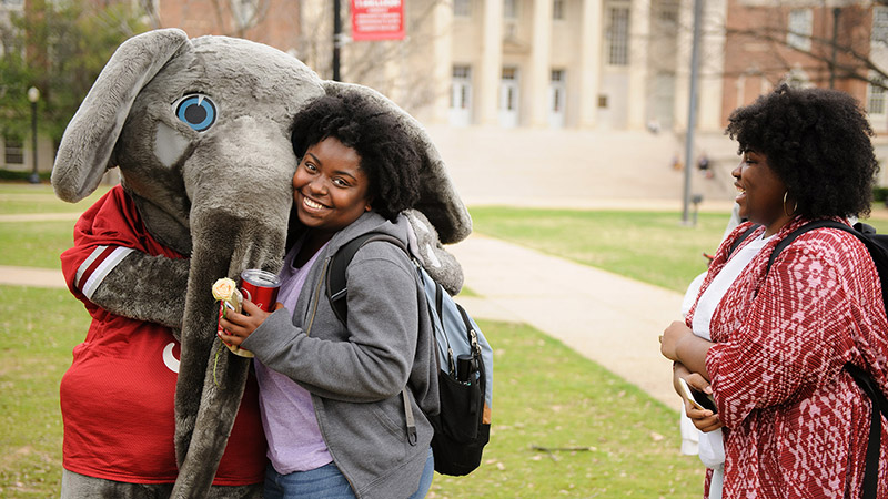 A student gets a hug from Big Al on the Quad